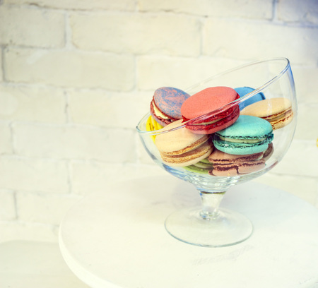 bright colored and marbled macaroons in a glass vase on a white brick background. 免版税图像