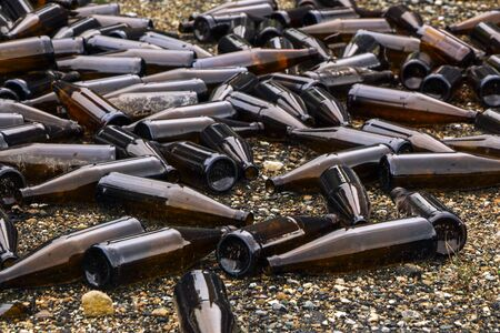 whole and broken brown bottles are scattered on the gravel.Concept: waste recycling, disposal of garbage