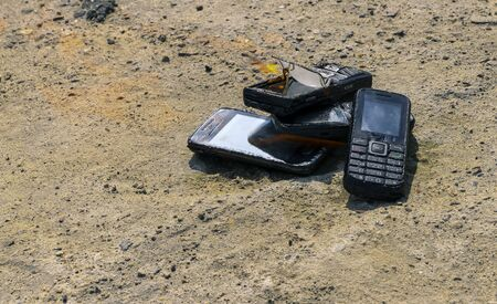burnt mobile phones on a textural concrete background. Concept: Danger of using low-quality cell phones.