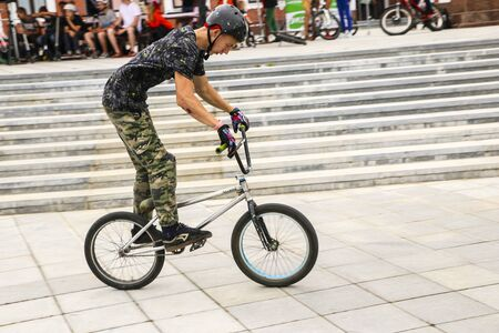 YOSHKAR-OLA, RUSSIA, AUGUST 10, 2019: teenagers guys perform interesting jumps and stunts on bicycles from ski jumps and ramps in a skate town.