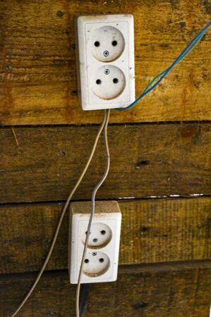 electrical outlets and switches made of white plastic on the wall in the room of an apartment or office, during repair. Stock Photo