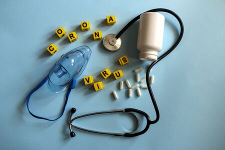 pills, stethoscope, thermometer, inhalation mask on a blue background with children`s yellow letters. Coronavirus 2019-nCoV disease and treatment concept.