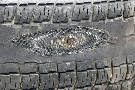 rubbed wheel of a lorry. worn wheel with a hole in the tire, worn rubber tread to the cord Stock Photo