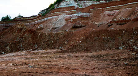 textures of various clay layers underground in  clay quarry after  geological study of the soil. colored layers of clay and stone in  section of the earth, different rock formations and soil layers.
