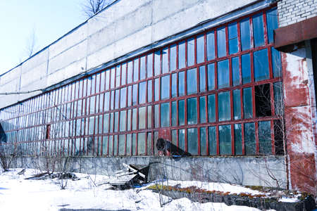 old, abandoned factory. Scattered glass, iron, wooden remains of production on floor, covered with snow and sawdust. Broken pipes, broken wiring, signal lights, broken roof and crane girder.