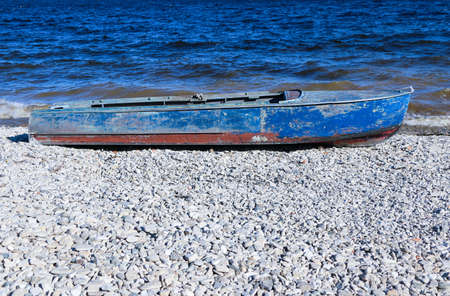 old rusty fishing boat lies on the pebble coast of the river. The waves of the tide roll over and break into spray and foam on the side, bow and stern of the boat.