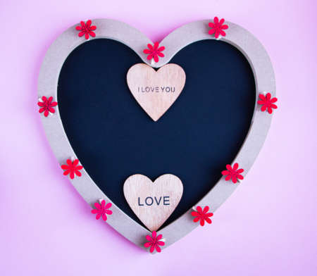 chalk board in the shape of a heart for copying space or writing congratulation text, with various red and pink accessories in the shape of a heart, for a postcard or congratulations on Valentines Day