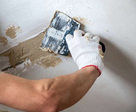 mans hand in a cloth glove with a spatula and putty, applies mastic to wall, ceiling to level surface. process of applying mastic with a spatula to surface for interior design of the room. Stock fotó