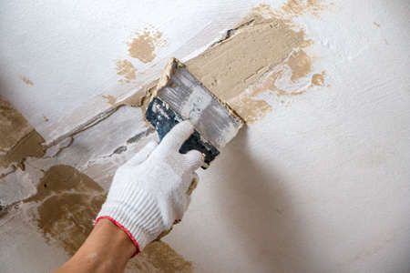 mans hand in a cloth glove with a spatula and putty, applies mastic to wall, ceiling to level surface. process of applying mastic with a spatula to surface for interior design of the room.