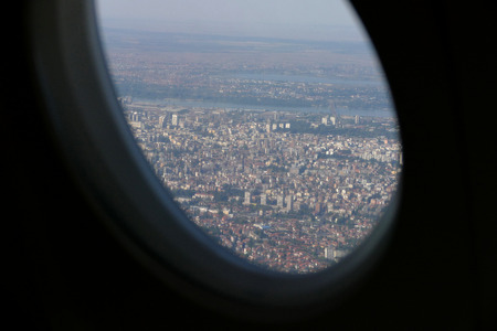 viewport: Beautiful city of Belgrade view with blue sky from plane window during decending