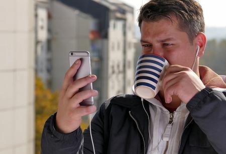 Man drinking coffee on a balcony