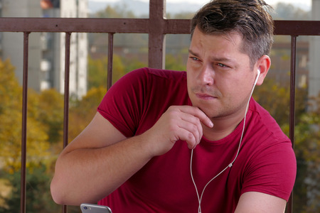 Man listening to music on a balcony