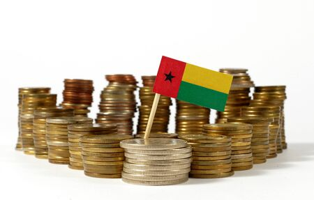 Guinea Bissau flag waving with stack of money coins Stock Photo