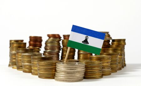 Lesotho flag waving with stack of money coins Stock Photo