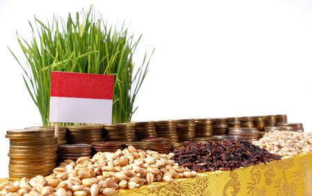 Monaco flag waving with stack of money coins and piles of wheat and rice seeds