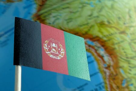 Afghanistan flag with a globe map as a background macro