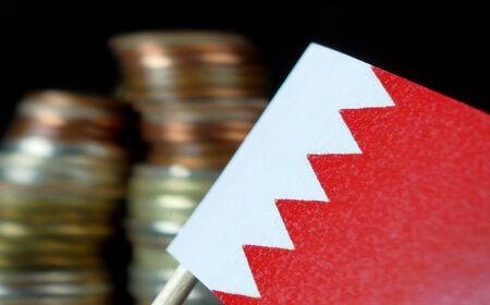 Bahraini flag waving with stack of money coins macro Stock Photo
