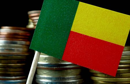 Benin flag waving with stack of money coins macro Stock Photo