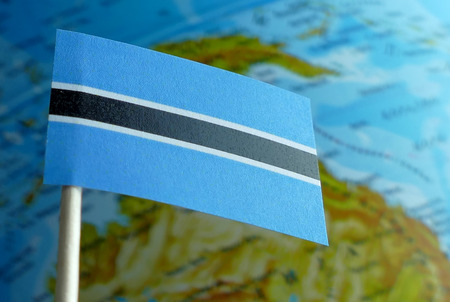 Botswana flag with a globe map as a background macro