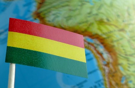 Bolivian flag with a globe map as a background macro