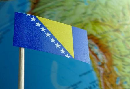 Bosnia and Herzegovina flag with a globe map as a background macro