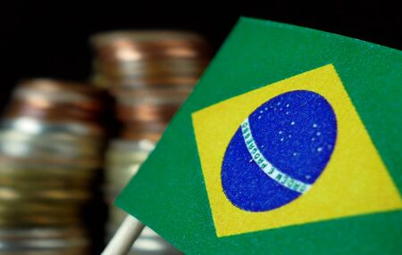 Brazilian flag waving with stack of money coins macro