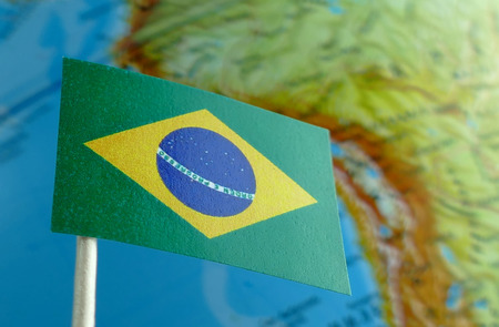 Brazilian flag with a globe map as a background macro