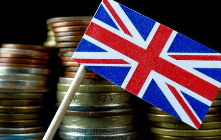 Great Britain flag waving with stack of money coins macro Фото со стока