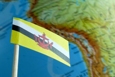 Brunei flag with a globe map as a background macro