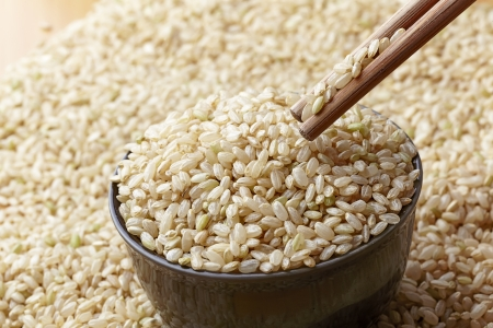 hulled: uncooked brown rice in a bowel and Chopsticks  with woody background Stock Photo