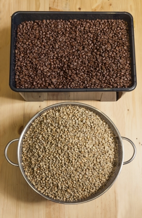 cofffee: one brescket of unroasted cofffee beans and one tray of roasted coffee bean  on woody table Stock Photo