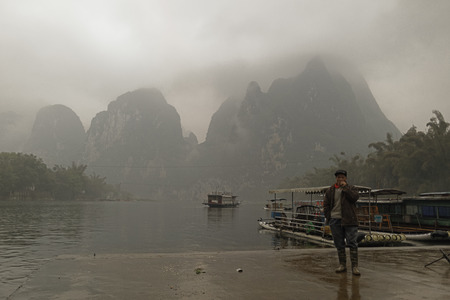 boatman: Li River,Guilin,China, 22th, March, 2014, boatman stands on the dock.  Li River scenery sight with fog in spring, Guilin, China Editorial