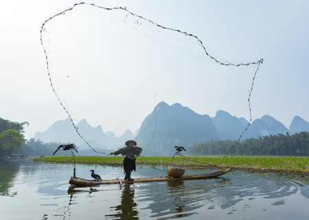 Cormorant, fish man and Li River scenery sight with fog in spring, Guilin, China Editorial