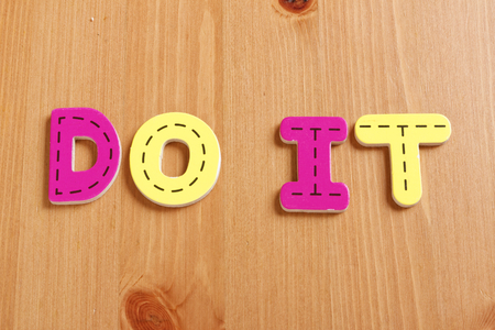 spell: DO IT, spell by woody puzzle letters with woody background Stock Photo