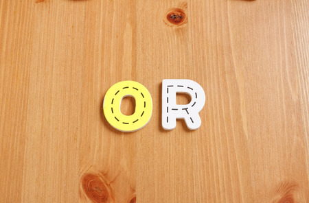 spell: OR, spell by woody puzzle letters with woody background Stock Photo