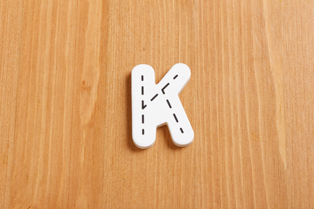 latter: K, spell by woody puzzle letters with woody background Stock Photo