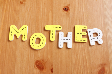 latter: MOTHER, spell by woody puzzle letters with woody background