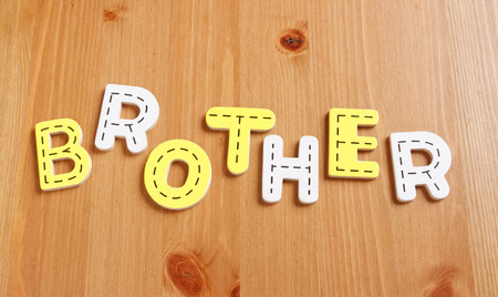 latter: BROTHER, spell by woody puzzle letters with woody background Stock Photo