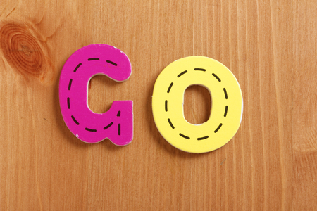 spell: GO, spell by woody puzzle letters with woody background Stock Photo