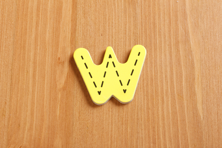latter: W, spell by woody puzzle letters with woody background Stock Photo