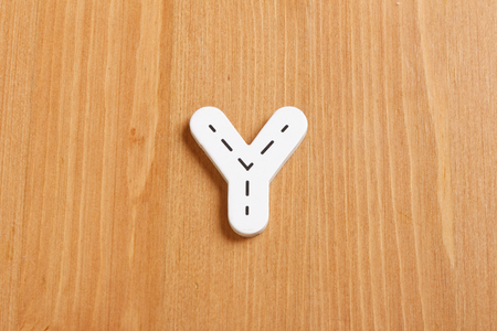 latter: Y, spell by woody puzzle letters with woody background Stock Photo