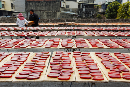 grey mullet: Beigang , Taiwan, January, 9th ,2014, Workers sort drying grey mullet roe on boards with sunlight