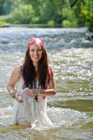Beautiful hippie girl with headscarf standing in a river photo