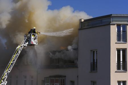 burning house: Two firefighters on a crane quench a burning house
