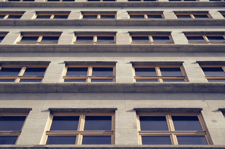 many windows: The facade of an office building with many windows in the style of the 40s