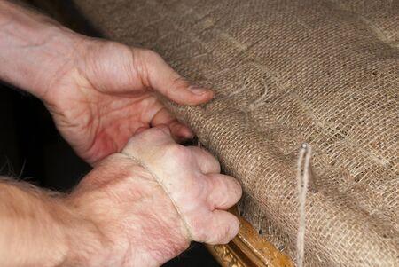 upholsterer: upholsterers hands restoring antique upholstery