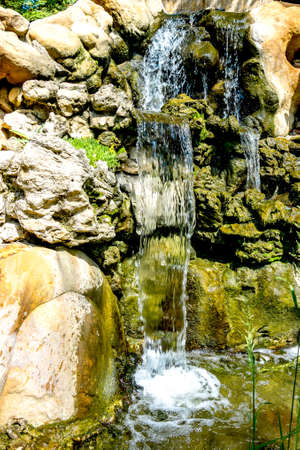 a waterfall in the park, giving coolness on a hot summer day waterfall