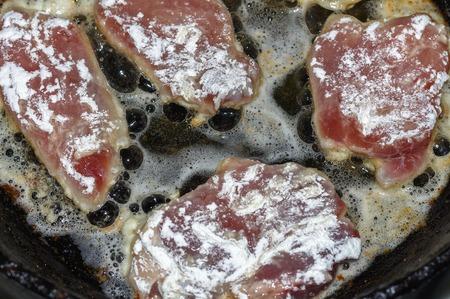 Raw fresh meat T-bone steak on cast iron frying pan on wooden background
