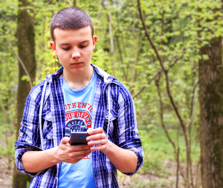 Young man stands in the woods, thinks about something and works on the phone