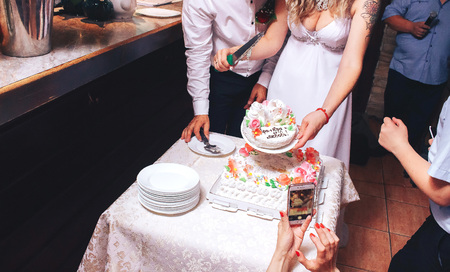 Happy wedding couple handsome groom and blonde bride carving delicious wedding cake